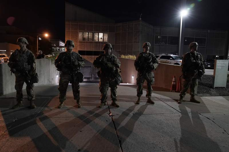 The National Guard protect the perimeter of government buildings in Kenosha, Wis. on Thursday, Aug. 27, 2020. People gathered for the fifth night to protest the Sunday police shooting of Jacob Blake. (AP Photo/Morry Gash)