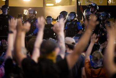 """Protesters demonstrating against police brutality raise their arms and chant, """"Don't shoot!"""" after Austin officers fired tear gas and rubber bullets at the crowd on May 30.      Miguel Gutierrez Jr./The Texas Tribune"""