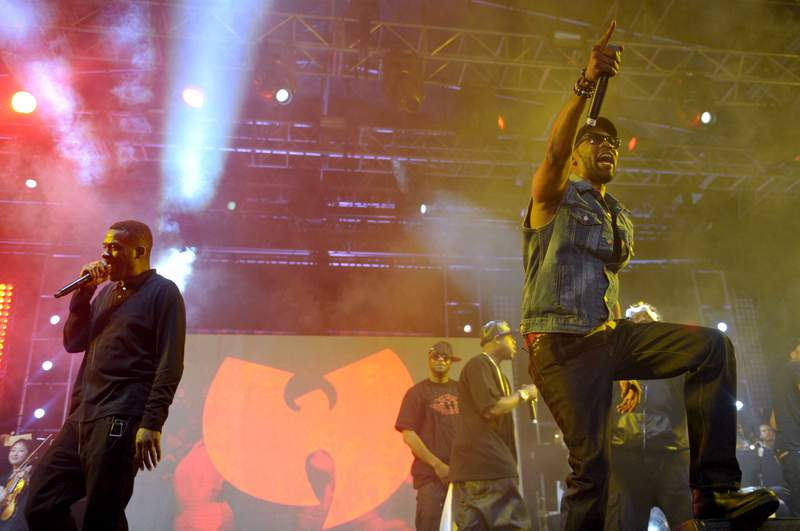 FILE - In this April 21, 2013, file photo, members of the Wu-Tang Clan perform on stage in front of their band logo at the Coachella Valley Music and Arts Festival at the Empire Polo Club in Indio, Calif. China has made a formal complaint to Canada over T-shirts with a similar bat-like logo ordered by a Canadian Embassy staffer in Beijing that allegedly mocked Chinas response to the coronavirus outbreak, in an apparent mix-up between the city of Wuhan and the hip-hop group. There are allegations the virus originated in bats and then spread to people in the city of Wuhan in late 2019. (John Shearer/Invision via AP)