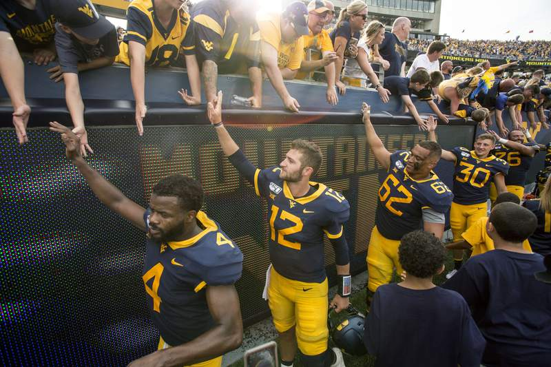 FILE - West Virginia football players celebrate with fans at the conclusion of an NCAA college football game against James Madison Aug. 31, 2019, in Morgantown, W.Va. A West Virginia program that received thousands of inquiries earlier this year from outdoor enthusiasts to move to the state in exchange for cash and other incentives has drawn dozens of newcomers to Morgantown and is taking applications for a second host city, Lewisburg. (AP Photo/Raymond Thompson, File)