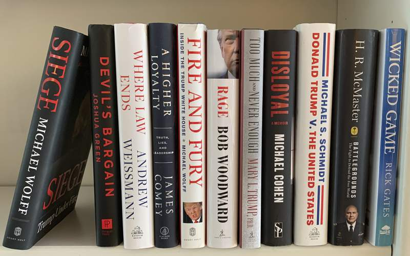 """A collection of books about President Donald Trump, from left, """"Siege"""" by Michael Wolff, """"Devil's Bargain"""" by Joshua Green, """"Where Law Ends"""" by Andrew Weissmann, """"A Higher Loyalty: Truth, Lies, and Leadership"""" by James Comey, """"Fire and Fury: Inside the Trump White House"""" by Michael Wolff, """"Rage"""" by Bob Woodward, """"Too Much and Never Enough"""" by Mary L. Trump, """"Disloyal"""" by Michael Cohen, """"Donald Trump V. The United States"""" by Michael S. Schmidt, """"Battlegrounds: The Fight to Defend the Free World"""" by H. R. McMaster and """"Wicked Game"""" by Rick Gates appear on a shelf in Westchester County, N.Y. on Monday, Nov. 9, 2020. One of publishing's most thriving genres of the past four years, books Trump, is not going to end when he leaves office. In 2021 look for waves of releases about the Trump administration and about the president's loss to Democratic candidate Joe Biden. (AP Photo)"""