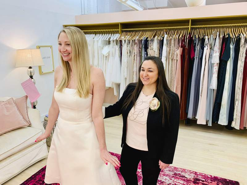 In this photo provided by Gilded Social, a bridal shop in Columbus, Ohio, owner Tanya Rutner Hartman helps customer Cristin Lee try on a gown at the shop on April 2, 2021. Although weddings and other big celebrations are going back on the calendar in the U.S., business owners who make those events happen expect a slow recovery from the impact of COVID-19. Hartman sees a shift in how couples feel about weddings, a change that can affect other businesses in the events industry as well. (Gilded Social via AP)