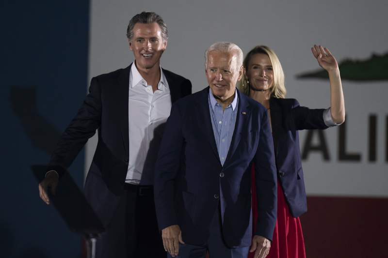FILE  In this Sept. 13, 2021, file photo President Joe Biden, center, smiles to the crowd as he is flanked by California Gov. Gavin Newsom and Jennifer Siebel Newsom at a rally ahead of the California gubernatorial recall election in Long Beach, Calif. In the recall election, Newsom won big in coastal urban areas such as Los Angeles County, while the pro-recall side performed better in California's Central Valley and northern areas. (AP Photo/Jae C. Hong, File)