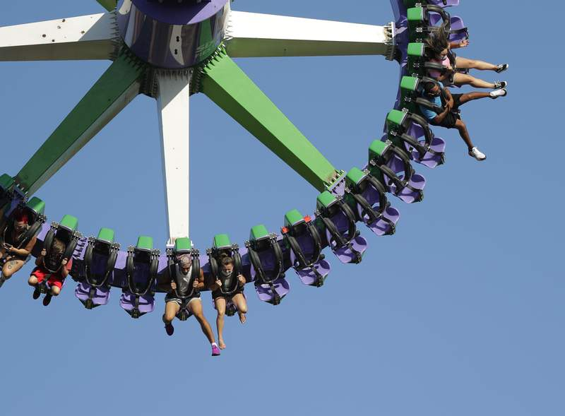 Visitors to Six Flag Fiesta Texas wear masks for protection against the coronavirus and are spaced apart on a ride Friday, June 19, 2020, in San Antonio. The theme park reopened Friday as COVID-19 cases continue to spike in Texas. (AP Photo/Eric Gay)