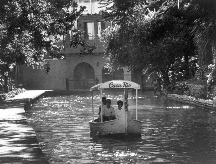 Photograph shows pleasure boat, owned by Casa Rio Restaurant, on river near Plaza Hotel.  Flood gate near W. Commerce Street in background. Photo circa 1960-1965. Photo courtesy UTSA Libraries Special Collections.