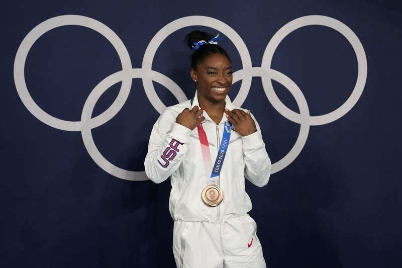 Simone Biles, of the United States, poses wearing her bronze medal from balance beam competition during artistic gymnastics at the 2020 Summer Olympics, Tuesday, Aug. 3, 2021, in Tokyo, Japan. (AP Photo/Natacha Pisarenko)