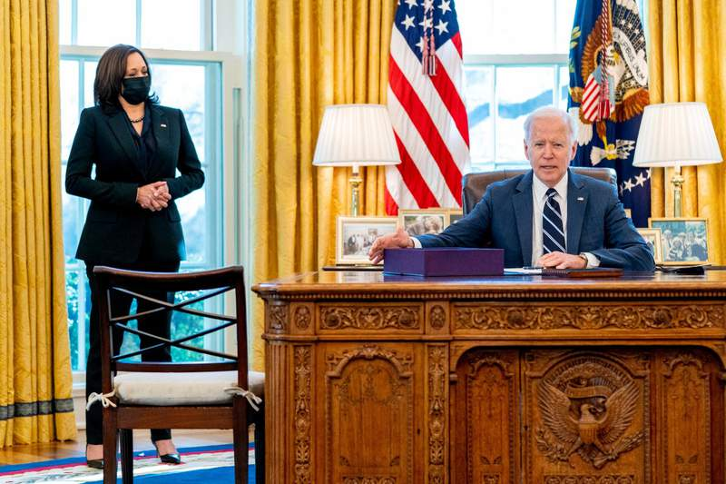 President Joe Biden, accompanied by Vice President Kamala Harris, looks up after signing the American Rescue Plan, a coronavirus relief package, in the Oval Office of the White House, Thursday, March 11, 2021, in Washington. (AP Photo/Andrew Harnik)