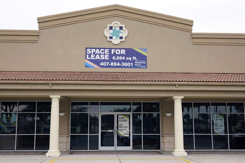 Signs advertise a business space for lease at a shopping plaza, Tuesday, Jan. 12, 2021, in Orlando, Fla.  The distribution of COVID-19 vaccines is fueling optimism that Americans will increasingly return to the ways they used to shop, travel and work before the pandemic. That would be a welcome change for companies that own office buildings and hotels, or those that lease space to restaurants, bars, department stores and other retailers.  (AP Photo/John Raoux)