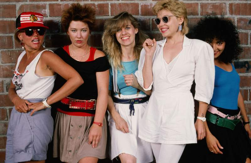 The Go-Gos, (L-R) Belinda Carlisle (lead vocals), Kathy Valentine (bass), Charlotte Caffey (lead guitar), Gina Schock (drums), and Jane Wiedlin (rhythm guitar), playfully pose during a 1985 Hollywood, California, portrait session. (Photo by George Rose/Getty Images)