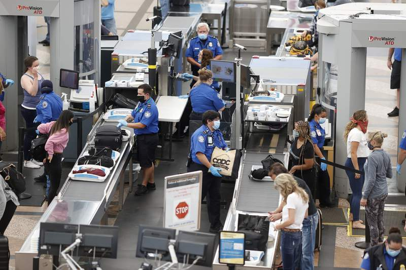 FILE - In this June 10, 2020 file photo, Transportation Security Administration agents process passengers at the south security checkpoint at Denver International Airport in Denver, as travelers deal with the effects of the new coronavirus. TSA, the government agency that oversees air travel, said the number of passengers screened for flights topped one million in a day on Sunday, Oct. 18 for the first time since the coronavirus pandemic outbreak last March.  (AP Photo/David Zalubowski, File)