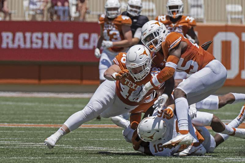 Texas defenders Jake Ehlinger, left, and B.J. Foster, right, tackle Kayvontay Dixon (16) during the first half of the Texas Orange and White Spring Scrimmage football game in Austin, Texas, Saturday, April 24, 2021. (AP Photo/Michael Thomas)