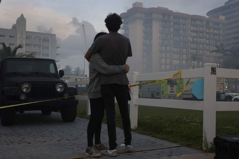 Biviana Faut, at left, and Christian Faut comfort each other as they look on at the partially collapsed 12-story Champlain Towers South condo building on June 25, 2021 in Surfside, Florida.