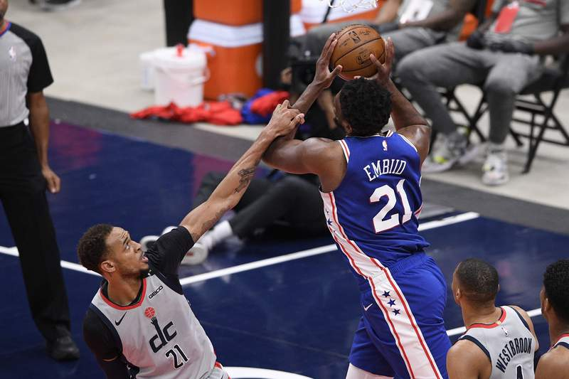 Philadelphia 76ers center Joel Embiid, right, is fouled by Washington Wizards center Daniel Gafford, left, during the first half of Game 4 in a first-round NBA basketball playoff series, Monday, May 31, 2021, in Washington. (AP Photo/Nick Wass)