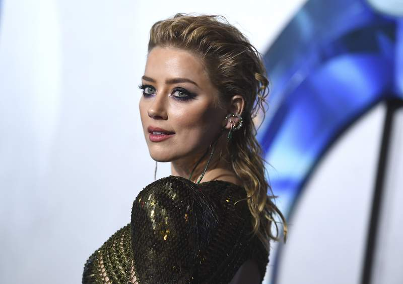 """FILE - Amber Heard arrives at the premiere of """"Aquaman"""" on Dec. 12, 2018, in Los Angeles. Heard says shes become a mom and did it on her own terms, as a single parent. In an Instagram post, the actor said she welcomed daughter Oonagh Paige Heard on April 8, 2021. (Photo by Jordan Strauss/Invision/AP, File)"""