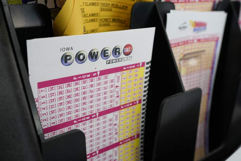 FILE - In this Jan. 12, 2021 file photo, blank forms for the Powerball lottery sit in a bin at a local grocery store, in Des Moines, Iowa. The giant Powerball jackpot has grown even bigger, with officials raising the estimated payout ahead of Saturday, Oct. 2, drawing.(AP Photo/Charlie Neibergall)
