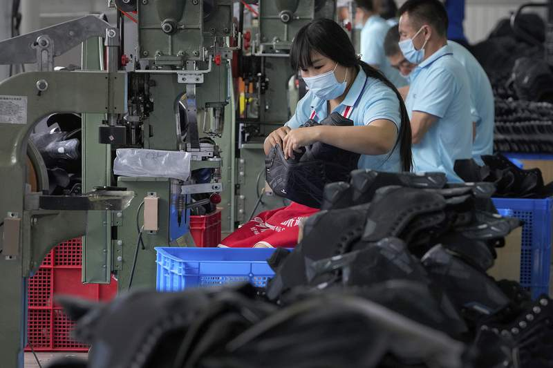 FILE - In this July 15, 2021, file photo, workers assembly ice-skating shoes at a manufacturing factory in the ice and snow sports equipment industry park in Zhangjiakou in northwestern China's Hebei province. Chinas manufacturing growth in July slowed to its lowest level in 15 months as export demand weakened and factories coped with disruptions in supplies of raw materials and components, two surveys found. (AP Photo/Andy Wong, File)
