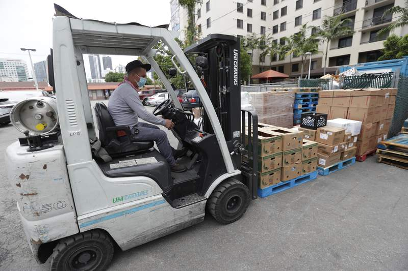 In this Wednesday, June 3, 2020 photo, a manager at the Presidente Supermarket uses a forklift to move a shipment of food at the store in the Little Havana neighborhood of Miami.  U.S. productivity fell at a 0.9% rate in the first three months of this year, a smaller decline than first estimated, while labor costs rose at a slightly faster pace. The Labor Department reported Thursday that the first quarter decline in productivity was smaller than the initial estimate a month ago of a 2.5% drop. Labor costs rose at a 5.1% rate, slightly faster than the 4.8% increase first reported.(AP Photo/Wilfredo Lee)