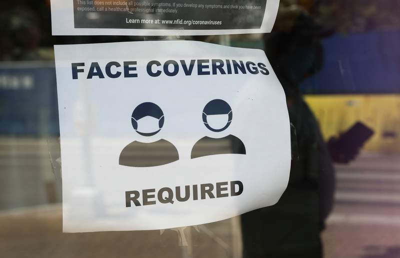 A visitor wearing a mask to protect against the spread of COVID-19 passes a sign requiring masks, Tuesday, July 7, 2020, in San Antonio. (AP Photo/Eric Gay)
