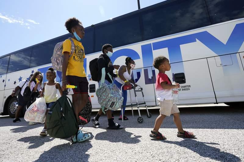 Evacuees walk to board buses Tuesday, Aug. 25, 2020, in Galveston, Texas. The evacuees are being taken to Austin, Texas, as Hurricane Laura heads toward the Gulf Coast. (AP Photo/David J. Phillip)