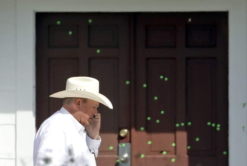 Wilson County Sheriff Joe Tackitt Jr. walks past the front doors where bullet holes were marked by police at the First Baptist Church, Tuesday, Nov. 7, 2017, in Sutherland Springs, Texas. A man opened fire inside the church in the small South Texas community on Sunday, killing more than two dozen and injuring others. (AP Photo/David J. Phillip)