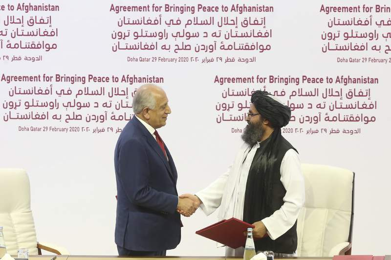 FILE - In this Feb. 29, 2020, file photo, U.S. peace envoy Zalmay Khalilzad, left, and Mullah Abdul Ghani Baradar, the Taliban group's top political leader shack hands after signing a peace agreement between Taliban and U.S. officials in Doha, Qatar. President Joe Biden and his national security team say the Trump administration tied their hands when it came to the U.S. withdrawal from Afghanistan. The argument that President Donald Trump's February 2020 deal with the Taliban set the stage for the weekend chaos that unfolded in Kabul has some merit. But, it's far from the full story. (AP Photo/Hussein Sayed, File)