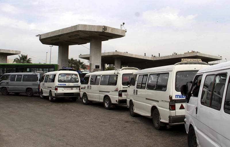 FILE - In this file photo released on April 7, 2019, by the Syrian official news agency SANA, shows vans queuing to fill their tanks with fuel, at a gas station in Daraa, south Syria.  On Sunday, Jan. 10, 2021, Syrias petroleum ministry blamed U.S. sanctions for forcing it to cut by up to 24% its distribution of fuel and diesel because of delays in arrival of needed supplies. (SANA via AP, File)