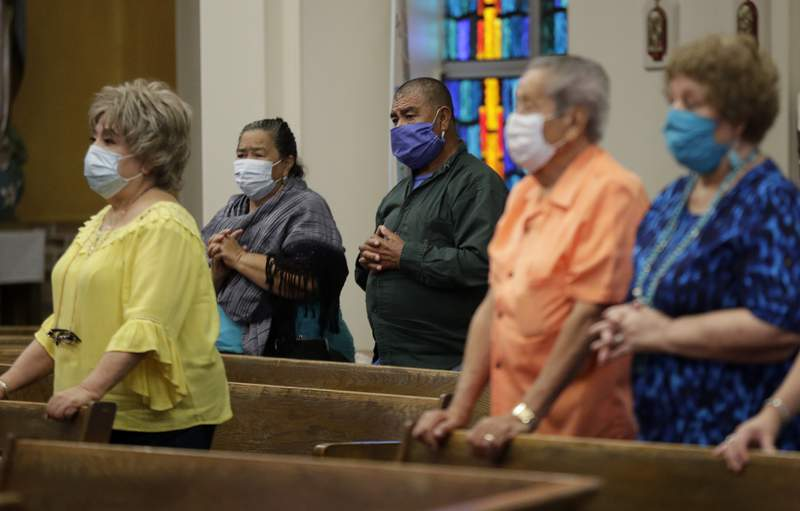 Parishioners wear face masks as they attend an in-person Mass at Christ the King Catholic Church in San Antonio, Tuesday, May 19, 2020. (AP Photo/Eric Gay)