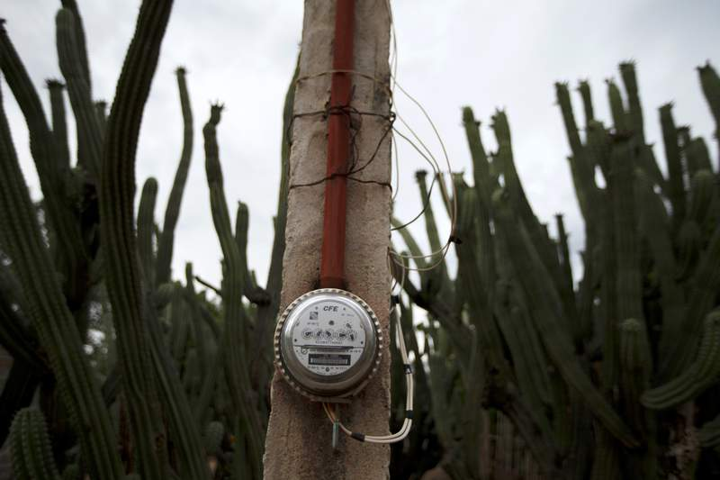 FILE - In this June 24, 2020 file photo, a Federal Electricity Commission or CFE electric meter is attached to a pole in San Jeronimo Xayacatlan, Mexico.  The International Chamber of Commerces Mexico chapter said Wednesday, March 10, 2021, the provisions of a new law favoring government-owned power generation over cleaner private electrical plants, violates Mexicos Constitution, which guarantees the right to competition and a healthy environment, and appears to violate investment-protection and trade agreements. (AP Photo/Fernando Llano, File)