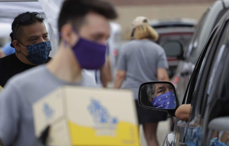 A driver wearing a bandana as protection is reflected in a mirror as volunteers help the San Antonio Food Bank distribute food to more that 2,000 at the Alamodome in San Antonio, Friday, April 17, 2020. San Antonio remains under stay-at-home orders due to the COVID-19 outbreak. (AP Photo/Eric Gay)