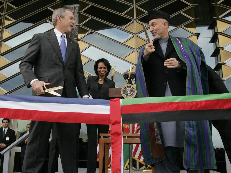 FILE - In this March 1, 2006 file photo, U.S. President George W. Bush, left and Afghan President Hamid Karzai get ready to cut a ribbon to officially open the U.S. Embassy in Kabul, Afghanistan. In an interview with German international broadcaster Deutsche Welle released Wednesday, July 14, 2021, Bush criticized the Western withdrawal from Afghanistan saying he fears that Afghan women and girls will suffer unspeakable harm. (AP Photo/Charles Dharapak, File)