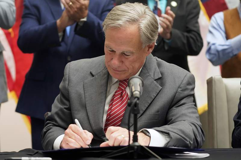 Texas Gov Greg Abbott signs Senate Bill 1, also known as the election integrity bill, into law in Tyler, Texas, Tuesday, Sept. 7, 2021.  The sweeping bill signed Tuesday by the two-term Republican governor further tightens Texas strict voting laws. (AP Photo/LM Otero)
