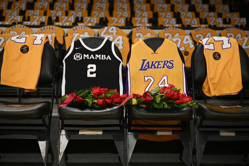 FILE - In this Jan. 31, 2020, file photo, the jerseys of late Los Angeles Laker Kobe Bryant, right, and his daughter Gianna are draped on the seats the two last sat on at Staples Center, prior to the Lakers' NBA basketball game against the Portland Trail Blazers in Los Angeles. A person with knowledge of the details says a public memorial service for Bryant, his daughter and seven others killed in a helicopter crash is planned for Feb. 24 at Staples Center. The Los Angeles arena is where Bryant starred for the Lakers for most of his two-decade career. The date corresponds with the jersey numbers he and 13-year-old daughter Gianna wore, 24 for him and 2 for her. (AP Photo/Kelvin Kuo, File)