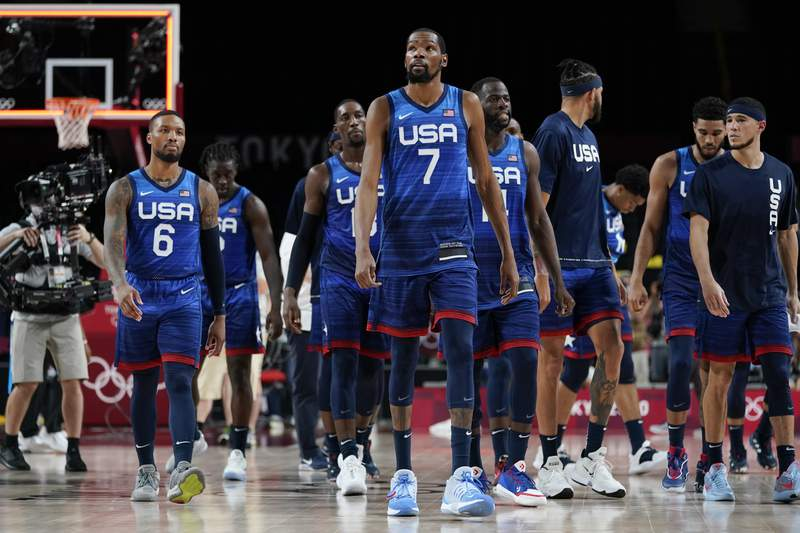 United States' Kevin Durant (7) walks off the court with teammates after a men's basketball preliminary round game against France at the 2020 Summer Olympics, Sunday, July 25, 2021, in Saitama, Japan. France won 83-76. (AP Photo/Charlie Neibergall)