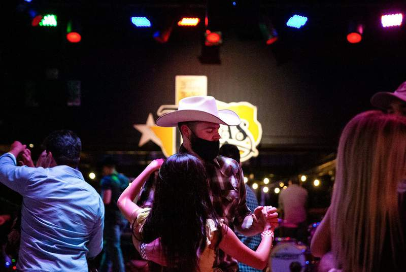 Guests dance at Billy Bob's Texas, a honky-tonk in Fort Worth. Billy Bob's was classified as a bar, but since Aug. 13 has operated under a food and beverage license. (Credit: Shelby Tauber for The Texas Tribune)