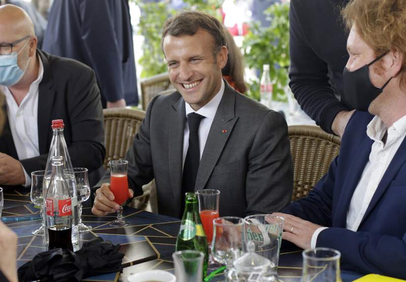 FILE - In this Friday, May 21, 2021 file photo, French President Emmanuel Macron shares a drink with shopkeepers during a visit to mark the reopening of cultural activities after closures during the Covid-19 pandemic, in Nevers, central France. With great relish and a straight face, France's president told a series of tall tales in a YouTube video that quickly went viral. Filmed in the French presidential palace with two of Frances most popular YouTube stars, the jovial half-hour of banter was Macrons most audacious effort yet to woo young voters.  (AP Photo/Thibault Camus, file)