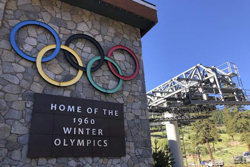 FILE - In this July 9, 2020, file photo, a sign marking the 1960 Winter Olympics is seen by a chairlift at Squaw Valley Ski Resort in Olympic Valley, Calif. A popular California ski resort whose name included a derogatory term for Native American women will be called Palisades Tahoe, resort officials announced Monday, Sept. 13, 2021, completing a new name search that began last year amid a reckoning over racial injustice. (AP Photo/Haven Daley, File)