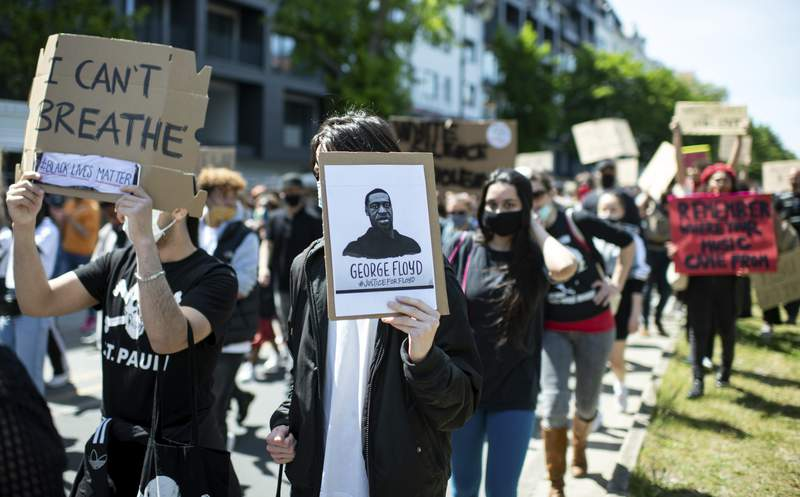 """People protest in Berlin, Germany, Sunday, May 31, 2020 after the violent death of the African-American George Floyd by a white policeman in the USA against racism and police violence, among other things with a sign """"I can't breathe"""". (Bernd von Jutrczenka/dpa via AP)"""
