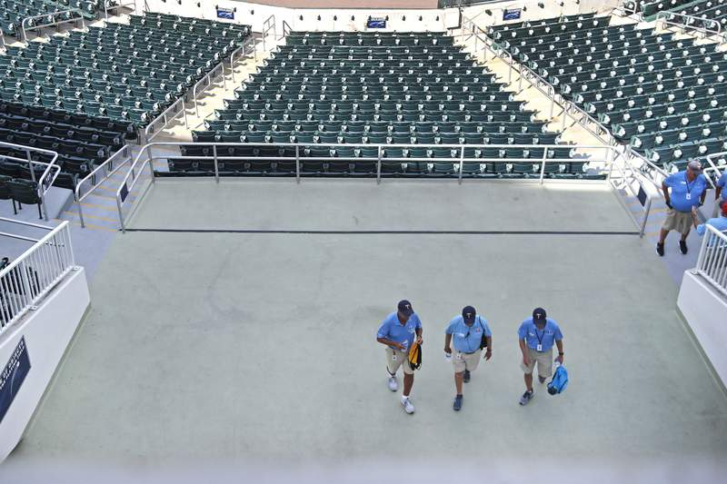 Ushers leave empty Hammond Stadium, after a baseball game between the Minnesota Twins and the Baltimore Orioles was canceled, Thursday, March 12, 2020, in Fort Myers, Fla. Major League Baseball has suspended the rest of its spring training game schedule because if the coronavirus outbreak. MLB is also delaying the start of its regular season by at least two weeks. (AP Photo/Elise Amendola)