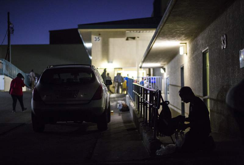FILE - This Oct. 15, 2019, file photo shows a patron of The Salvation Army homeless shelter, right, checking his belongings at a shelter near downtown Las Vegas. Amid protests that they would criminalize being homeless, Las Vegas elected officials are poised to make it a misdemeanor for people to sleep or camp in public areas when beds are available at established shelters. (Chase Stevens/Las Vegas Review-Journal via AP, File)