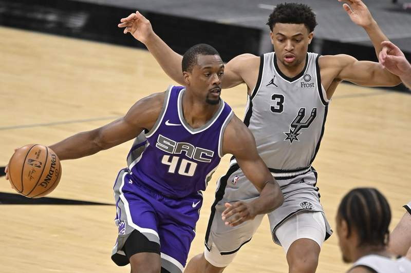 Sacramento Kings' Harrison Barnes (40) drives around San Antonio Spurs' Keldon Johnson during the second half of an NBA basketball game on Monday, March 29, 2021, in San Antonio.