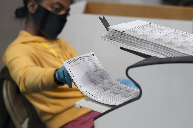 FILE - In this Nov. 5, 2020, file photo, a county election worker scans mail-in ballots at a tabulating area at the Clark County Election Department in Las Vegas. The U.S. Census says more than two-thirds of U.S. citizens cast a ballot in the 2020 presidential election. And 7 out of 10 who voted did so by mail or at a polling place before Election Day. (AP Photo/John Locher, File)