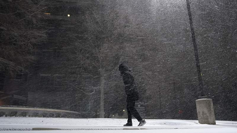 A woman walks through falling snow in San Antonio, Sunday, Feb. 14, 2021. Snow and ice blanketed large swaths of the U.S. on Sunday, prompting canceled flights, making driving perilous and reaching into areas as far south as Texas' Gulf Coast, where snow and sleet were expected overnight. (AP Photo/Eric Gay)